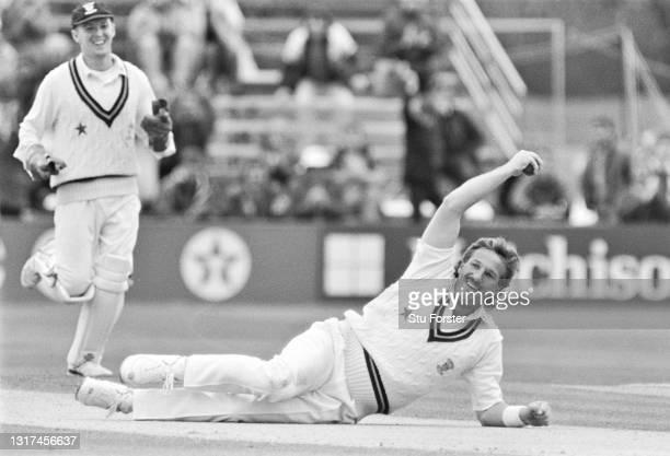 Durham player Ian Botham celebrates after catching out Glamorgan batsman Viv Richards off his own bowling for 1 run as wicketkeeper Chris Scott runs...
