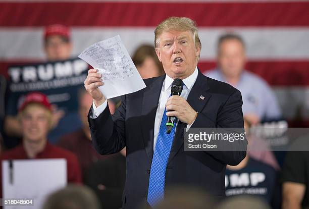 During a campaign rally Republican presidential candidate Donald Trump reads a statement made by Michelle Fields a former reporter for Breitbart News...