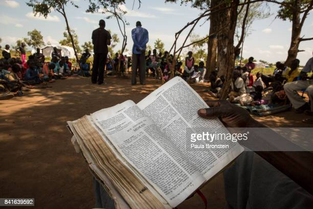 During a Catholic Sunday prayer service held under the shade of a tree refugees sit and pray as priests deliver their sermonThe Onward Struggle A...