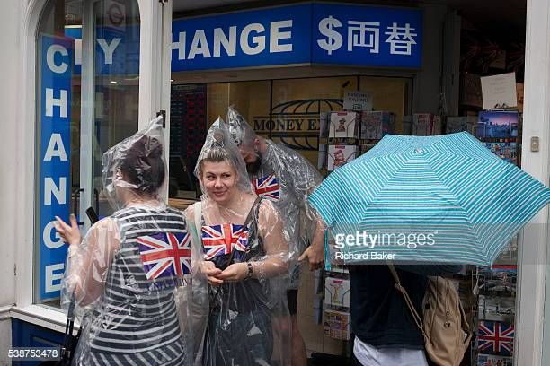 During a downpour an afternoon of heavy rainfall in London a group of three tourists wearing matching plastic macs with Union jack flags emerge from...