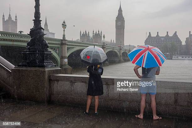 During a downpour an afternoon of heavy rainfall in London a wet man stands in a puddle overlooking the River Thames and parliament from London's...