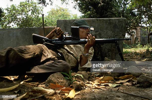 During a firefight in Usulatan El Salvador and Treasury Policeman peer around the cornor of a washstand towards nearby guerrillas