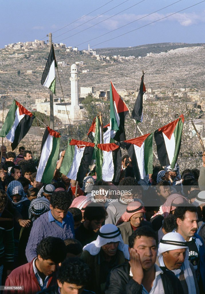 During a funeral procession, mourners carrying Palestinian Liberation Organization flags protest the death of a Palestinian killed during the uprising in Ramallah. Violence broke out after rebel Israeli and Palestinian fighters protested in the disputed territory of West Bank during the first Intifada.