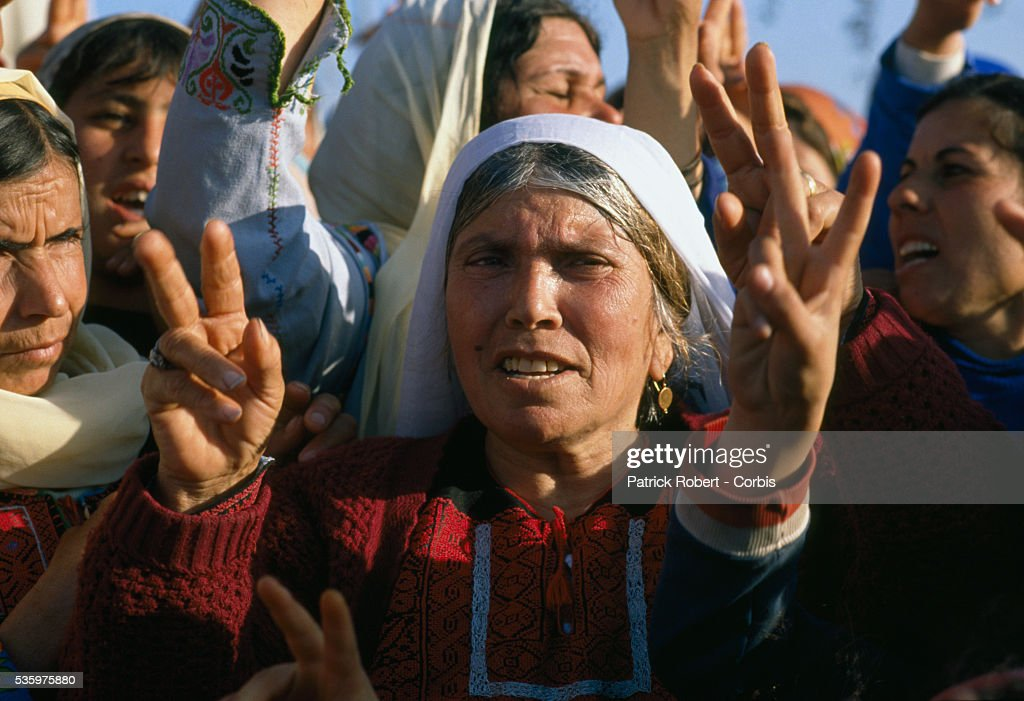 During a funeral procession, mourners give peace signs and protest the death of a Palestinian killed during the uprising in Ramallah. Violence broke out after rebel Israeli and Palestinian fighters protested in the disputed territory of West Bank during the first Intifada.