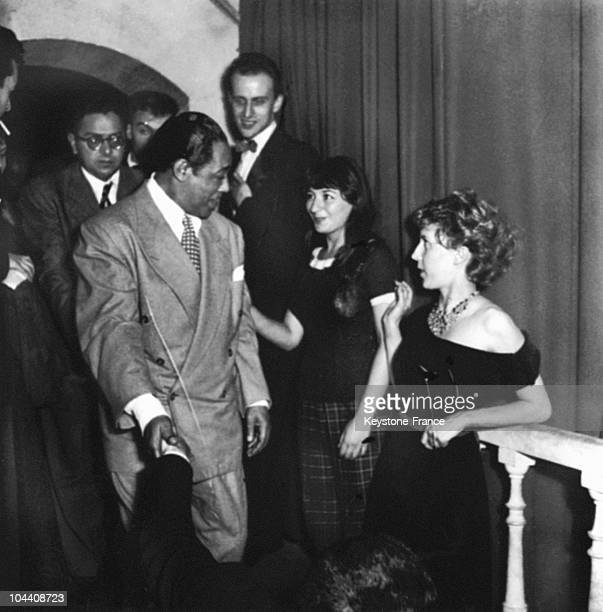 During a gala organized in his honor at the Club SaintGermaindesPres in Paris American jazz composer and pianist Duke ELLINGTON is congratulated by...