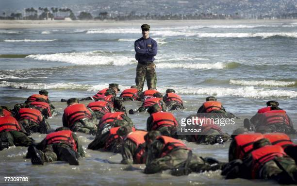 During a Hell Week surf drill evolution, a Navy SEAL instructor assists students from Basic Underwater Demolition/SEAL class 245 with learning the...