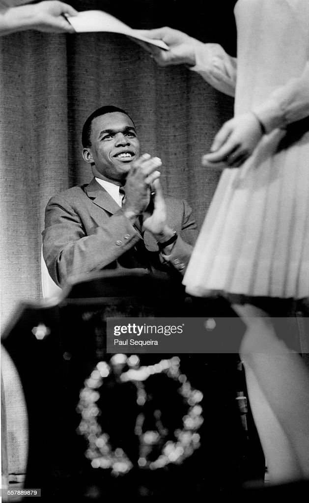 During a high school awards program, American football player Gale Sayers, of the Chicago Bears, applauds a student, Arlington Heights, Illinois, 1967.