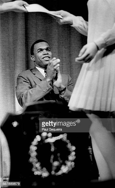 During a high school awards program American football player Gale Sayers of the Chicago Bears applauds a student Arlington Heights Illinois 1967