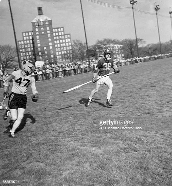During a lacrosse game a Loyola defenseman goes for Johns Hopkins Cocaptain and attackman Byron Forbush on the Homewood Field in Baltimore Maryland