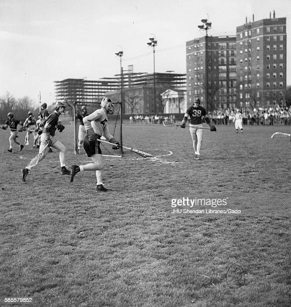 During a lacrosse game, a Loyola defenseman goes for Johns Hopkins Co-captain and attackman Byron Forbush , on the Homewood Field in Baltimore,...