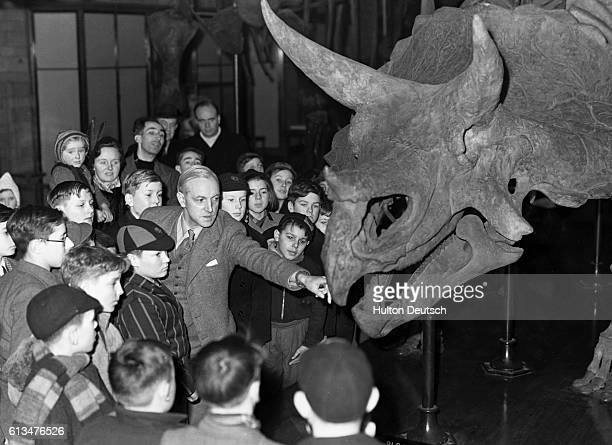 During a lecture held for children at the Natural History Museum entitled The Lost World Dr W E Swinton shows them the skeleton of a giant...