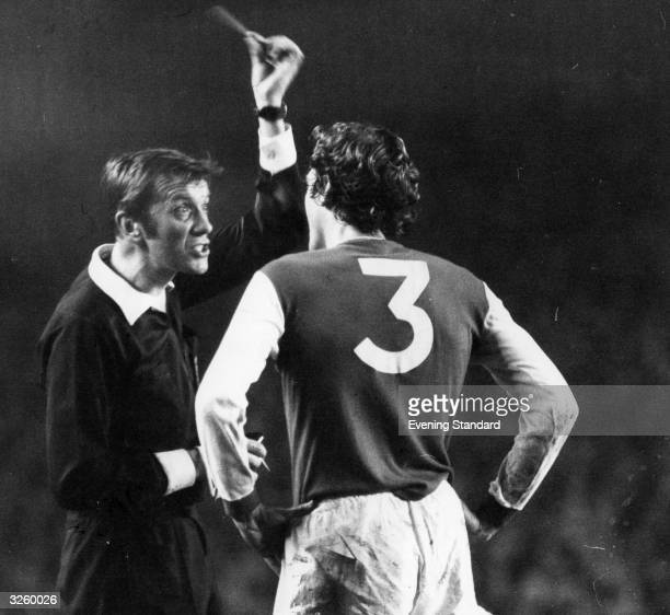 During a match between London football clubs Arsenal and Chelsea Arsenal player Sammy Nelson is booked by referee Ray Toseland who holds up the...