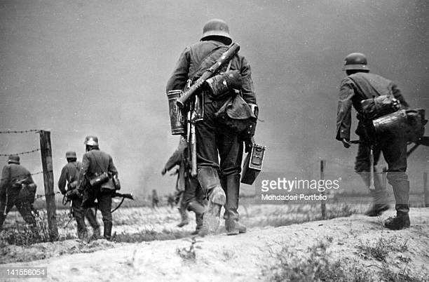 During a military action in 'No man's Land' German patrol protected from artillery explosions advancing in a breach grid France October 1939