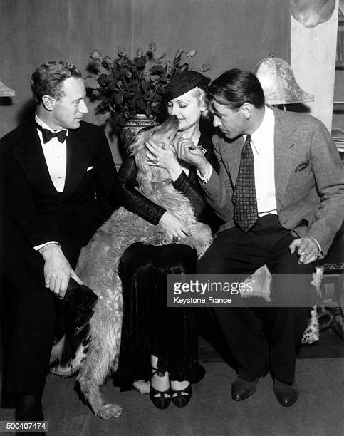 During a party for the American actress Mary Pickford Leslie Howard Carole Lombard and Gary Cooper are stroking his dog on July 02 1933 in Los...