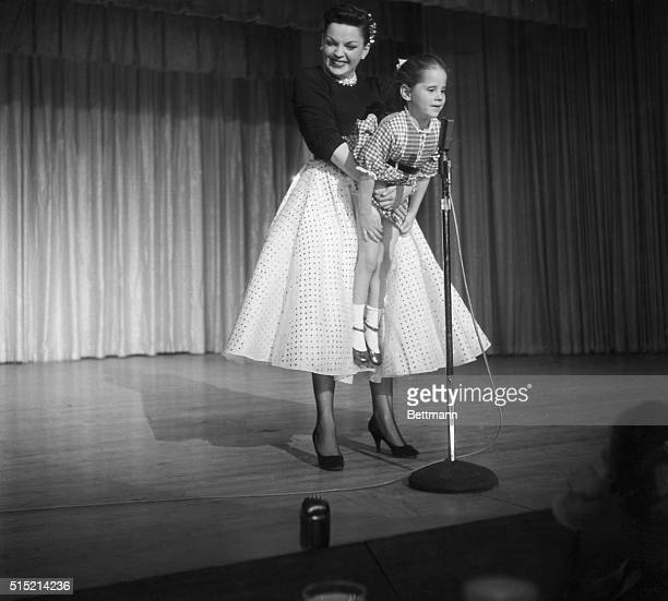During a performance Judy Garland holds her daughter up to the microphone to sing Jingle Bells after spotting her in the audience