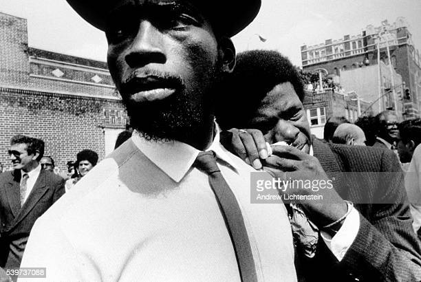 During a period of intense racial tension in New York City two men weep in the street outside of the church where funeral services are being held for...