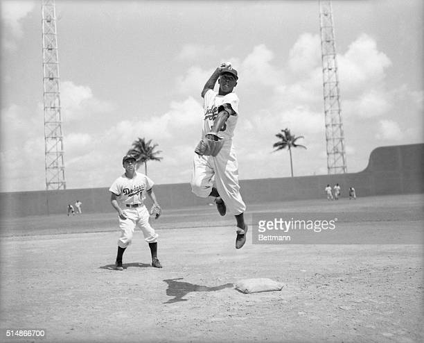 During a practice at spring training Brooklyn Dodgers shortstop Pee Wee Reese looks on as second baseman Jim Junior Gilliam completes a double play...