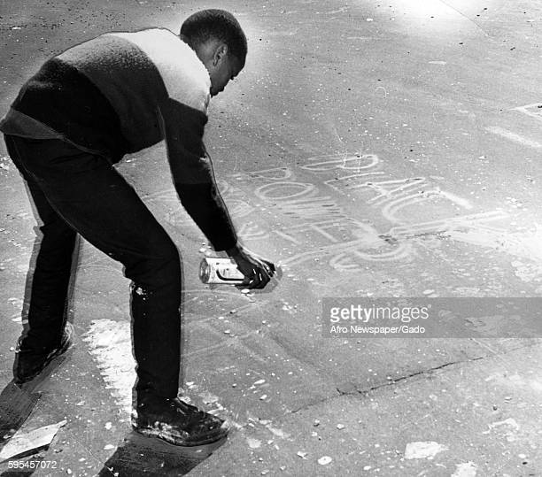 During a raciallymotivated riot in Baltimore Maryland an AfricanAmerican youth uses a spray paint can to pain the slogan Black Power on a sidewalk in...
