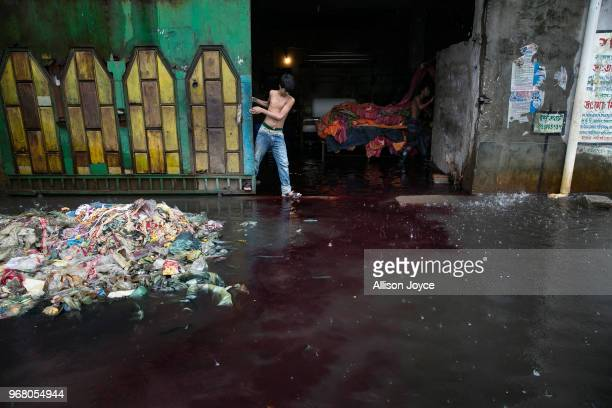 During a rainstorm color washes out of a dying factory in Shyampur whose waste is dumped into the Buriganga river on June 4 2018 in Dhaka Bangladesh...