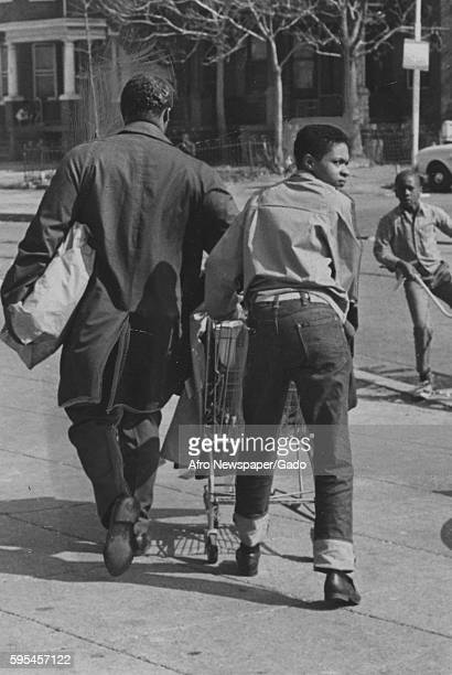 During a riot in Baltimore, Maryland, two African-American men use a shopping cart to carry off looted goods, Baltimore, Maryland, 1943.