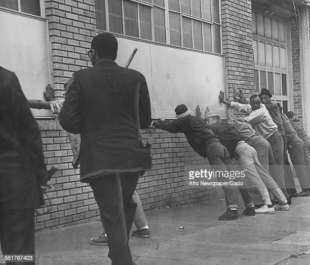 During a riot police officers with billy clubs guard suspected looters who stand with their hands against a brick wall at the corner of Howard and...