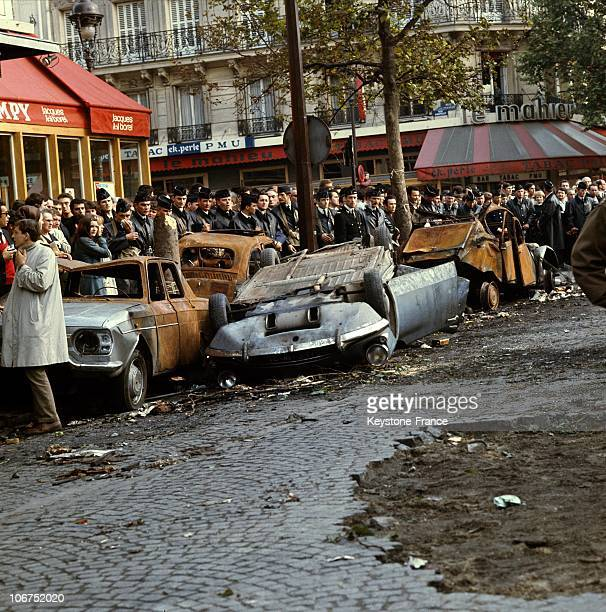 During A Student Demonstration On Boulevard Saint Michel In Paris, Members Of The Crs Were Positioned Behind Burnt Out Cars At The Corner Of Rue...