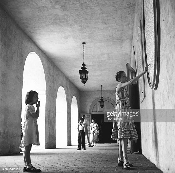 During a tour of the Wren Building at the College of William and Mary a girl points out details on a sign to her younger sister Williamsburg Virginia...