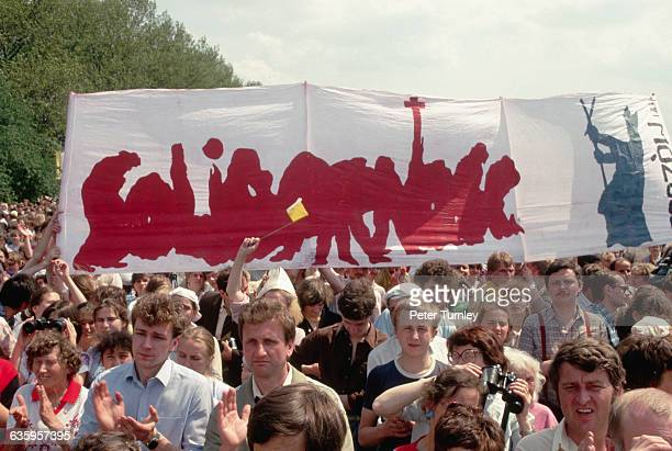 During a visit from Pope John Paul II demonstrators march down a street carrying banners reading Solidarnosc the name of the first Polish trade union...