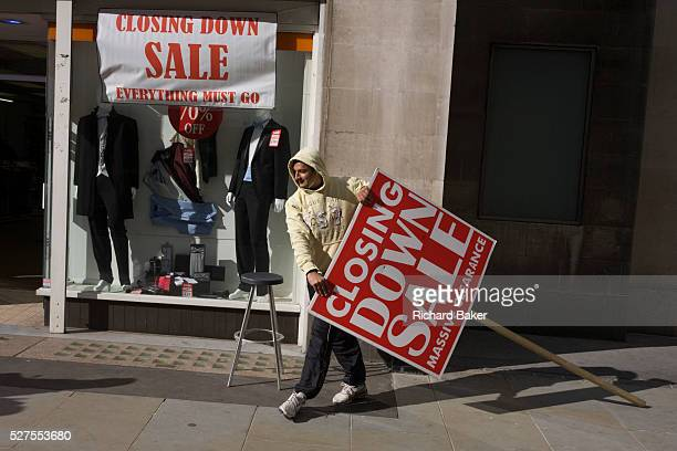 During a windy afternoon a sandwich board man holds his broken sign for a menswear shop's closure sale in central London After spending the afternoon...
