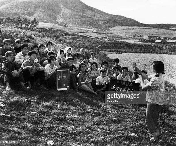 During a work break a young woman is leading the commune workers in singing a song praising chairman mao cultural revolution tachai shansi province...