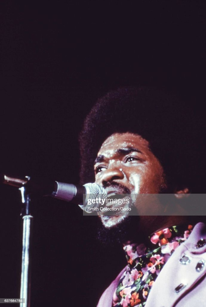 During an annual Black Talent Expo, a male singer wearing floral shirt and studded lavender blazer feels the heat on stage, sweating from the brow beneath his tall Afro, singing into the microphone with a gaze out into the crowd, Chicago, Illinois, 1973. Image courtesy National Archives. (Photo via Smith Collection/Gado/Getty Images).