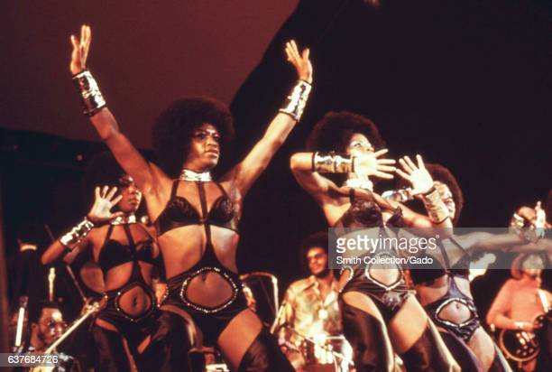 During an annual Black Talent Expo female dancers for soul singer Isaac Hayes shine on stage in black leather body suits tall boots shiny cuffs and...