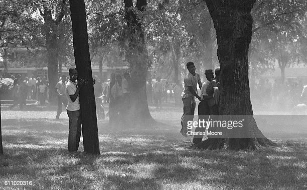 During an antisegregation demonstration in Kelly Ingram Park young men take refuge from firehoses behind trees Birmingham Alabama early May 1963...