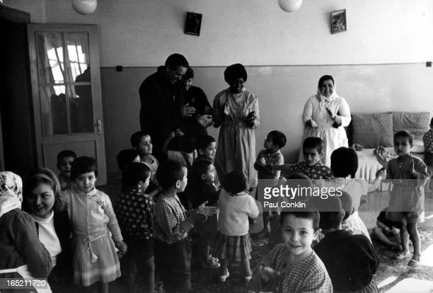 During an aroundtheworld trip to visit Peace Corps volunteers Peace Corps founder and president Sargent Shriver stops at an orphanage where volunteer...