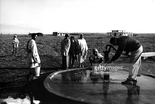 During an aroundtheworld trip to visit Peace Corps volunteers Peace Corps founder and president Sargent Shriver pumps water at a well near an...