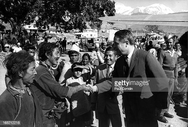 During an aroundtheworld trip to visit Peace Corps volunteers Peace Corps founder and president Sargent Shriver shakes hands with Tibetan porter at...