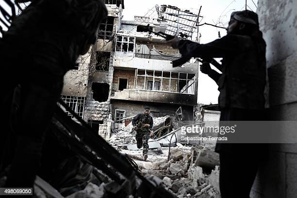 During an exchange of small arms fire with forces loyal to the Syrian regime a exposed FSA fighter quickly moves from one building to another while...