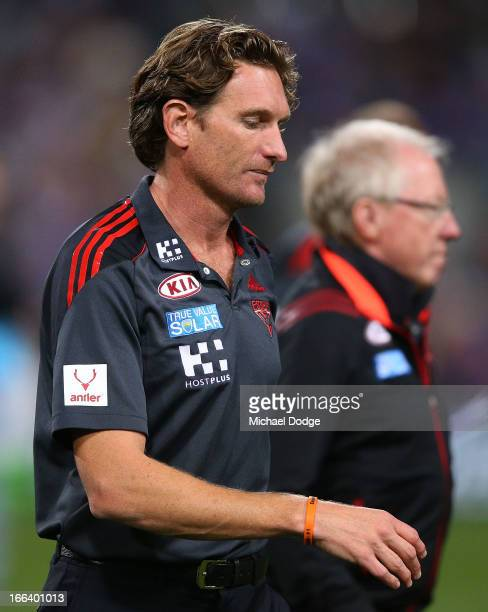 during Bombers coach James Hird walks back from their quarter time huddle next to Dr Bruce Reid during the round three AFL match between the...