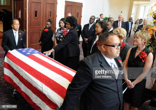 During Federal Judge Matthew J Perry's funeral at Brookland Baptist Church mourners stand as Michael Perry wheels his father's flagdraped casket past...