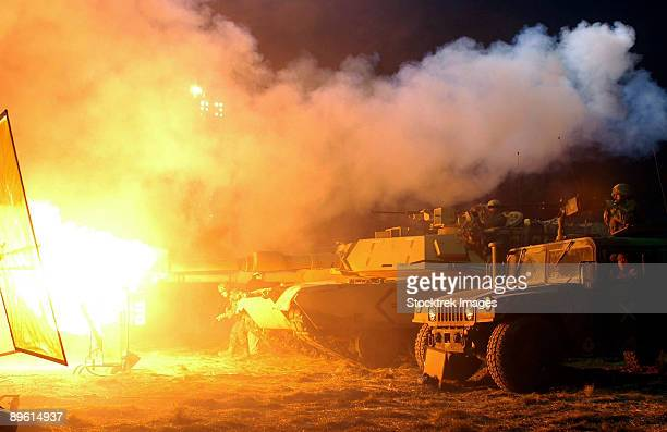 during filming, marines fight aliens with a torrent of heavy tank and machine gunfire. to the left of the picture is the production company's lights added for battlefield effect. - battlefield stock pictures, royalty-free photos & images
