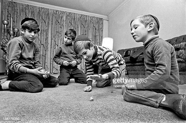 During Hanukkah the four sons of a Jewish family spin a foursided spinning top called a dreidel Brookline Massachusetts 1971
