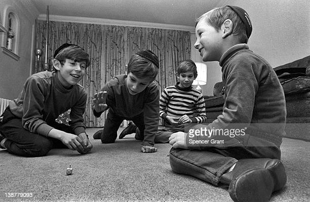 During Hanukkah, the four sons of a Jewish family spin a four-sided spinning top called a dreidel, Brookline, Massachusetts, 1971.