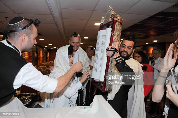During his Bar Mitzvah ceremony a boy reaches toward a Torah scroll held aloft by a rabbi Jerusalem Israel November 5 2015 The man in center rear is...