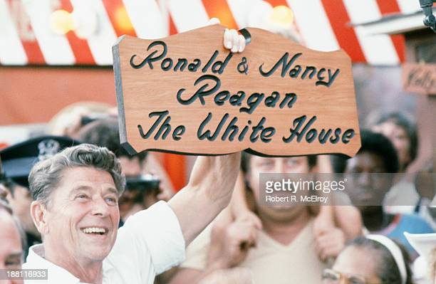 During his presidential campaign American politician Ronald Reagan holds up a personalized wooden sign at the Michigan State Fair Ionia Michigan...