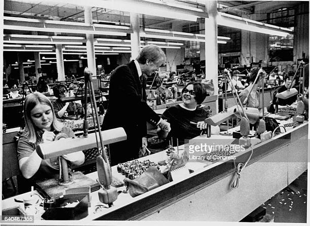 During his presidential campaign Jimmy Carter shakes hands with a factory worker who makes costume jewelry