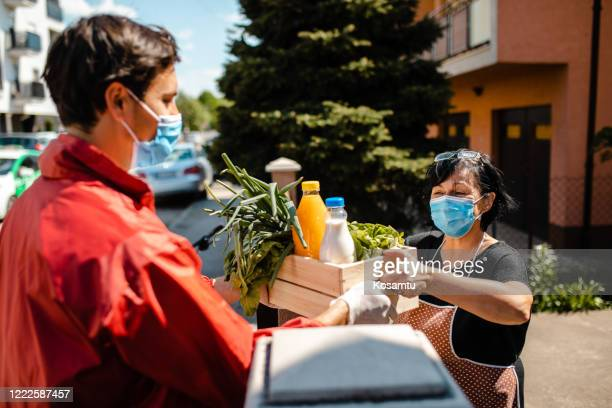 during home isolation senior people can't go out, so volunteer from health service deliver them a crate of fresh groceries - food distribution stock pictures, royalty-free photos & images