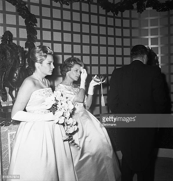 During lull in guest arrivals Mrs Henry Ford II dabs at her makeup while Charlotte 9left watches