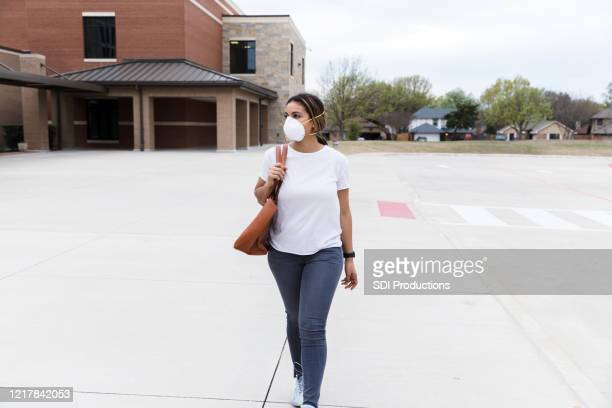 during pandemic, teacher wearing mask walks by empty school - state school stock pictures, royalty-free photos & images
