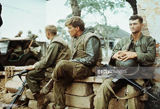 During pause in fighting between allied and communist troops two young US Marines their faces reflecting their weariness sit sadfaced and idle for a...
