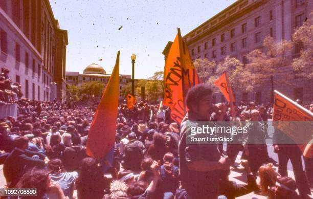 During the 1971 May Day Protests against the Vietnam War a crowd of male and female protestors sit together on a sunny day on 10th St NW in between...